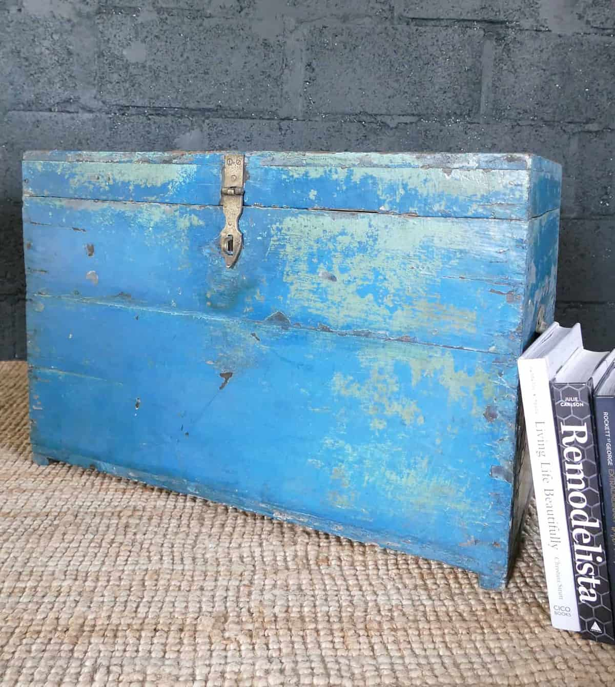 closed blue box with books leaning on it