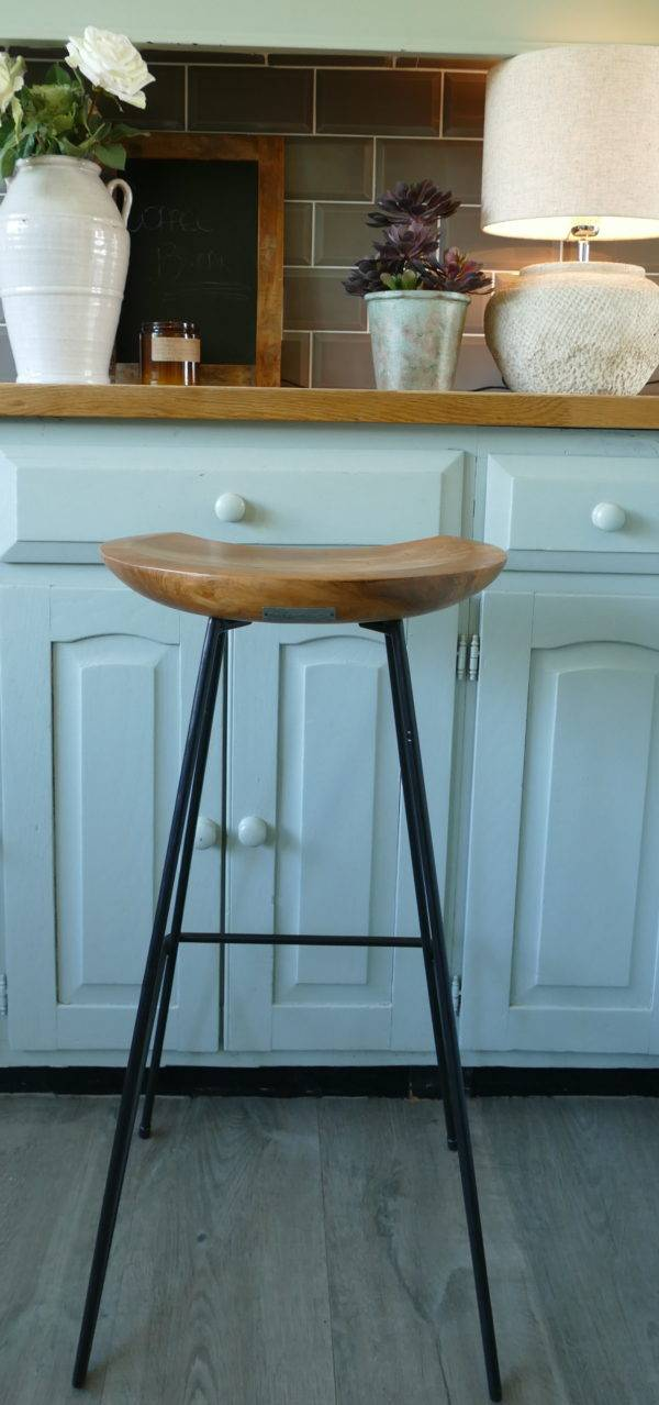 teak bar stool at blue counter