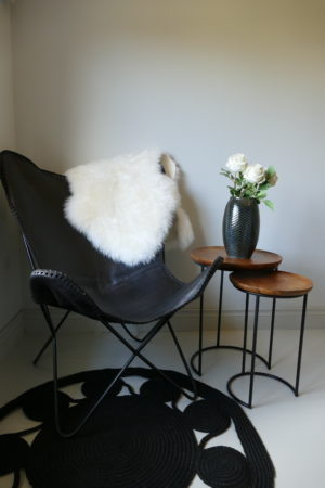 butterfly shaped black leather chair beside side tables
