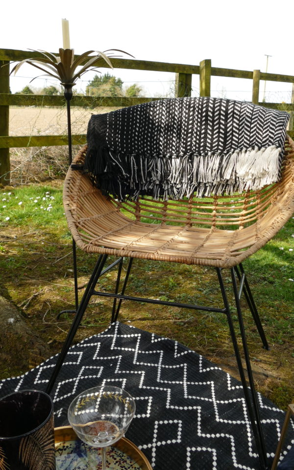 jane bucket outdoor chair on black and white blanket