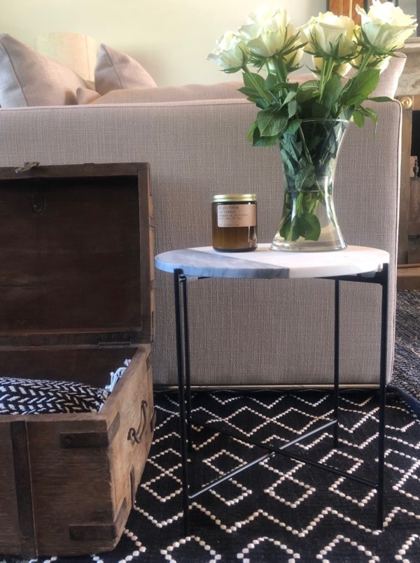 marble side table with white roses on dark rug