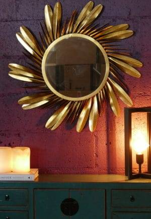 gold round mirror with feathers