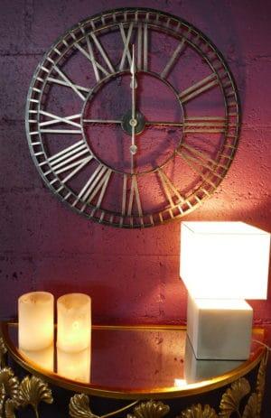 Large black roman numeral clock on purple wall