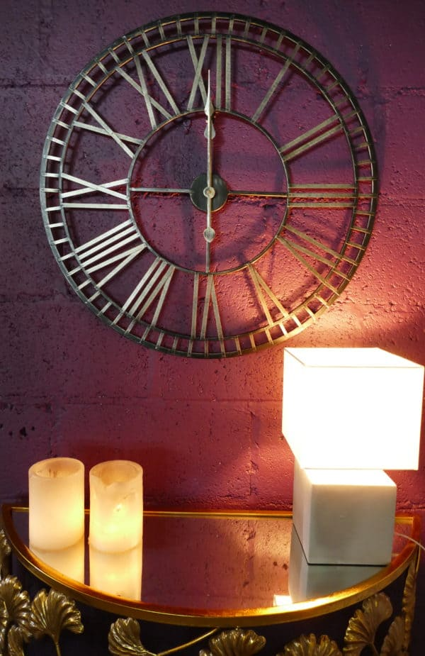 Large black roman numeral clock on purple wall