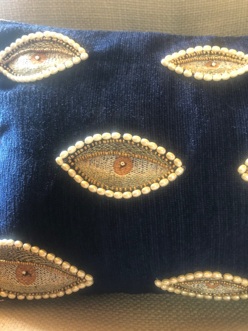 close up of stitched eye design on eye can see you cushion
