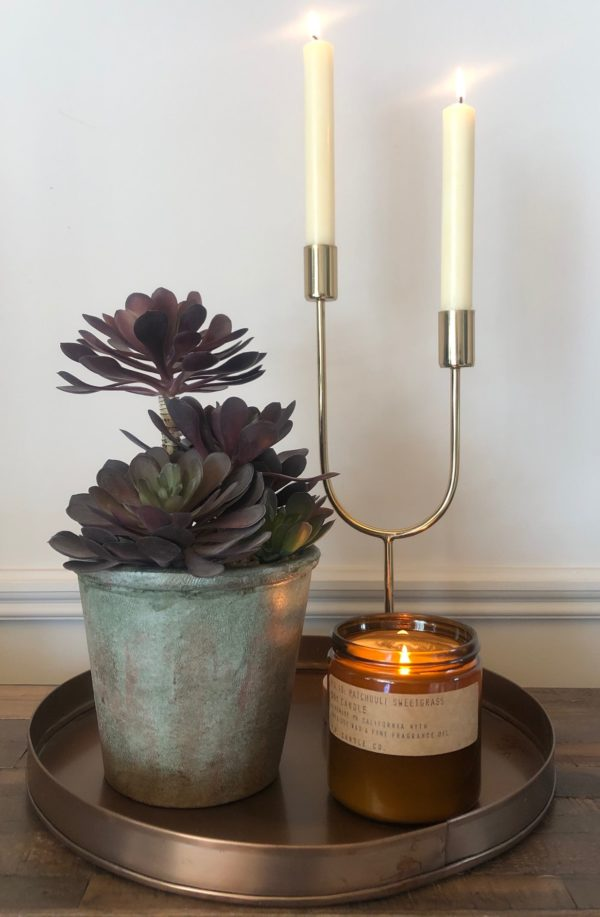 faux floral plant beside candle sticks
