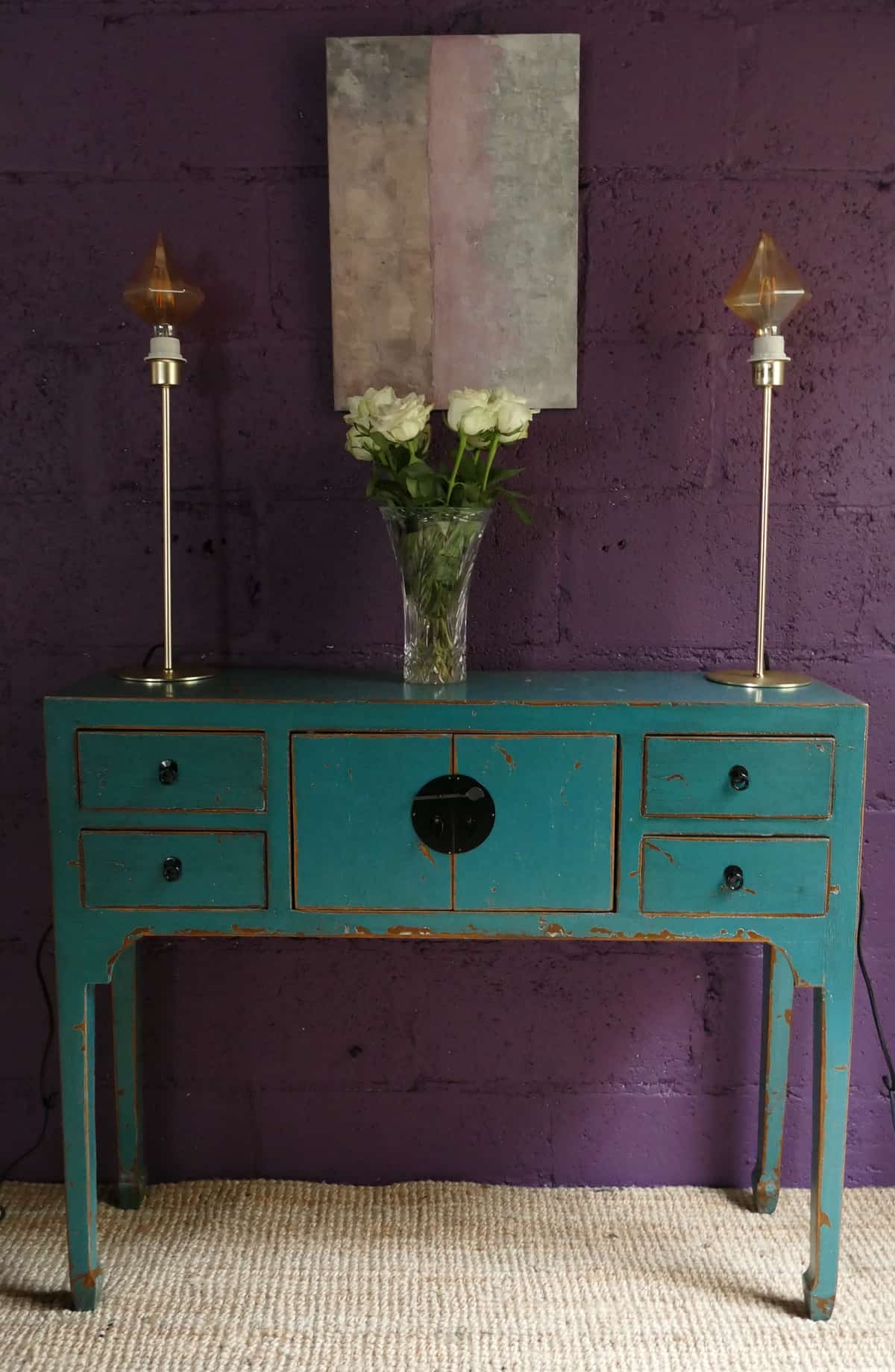 distressed blue dresser and vase of white roses