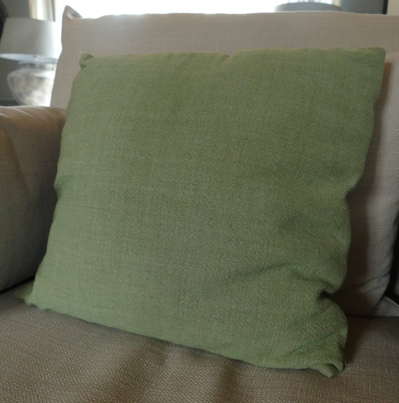 green twill square cushion on sofa