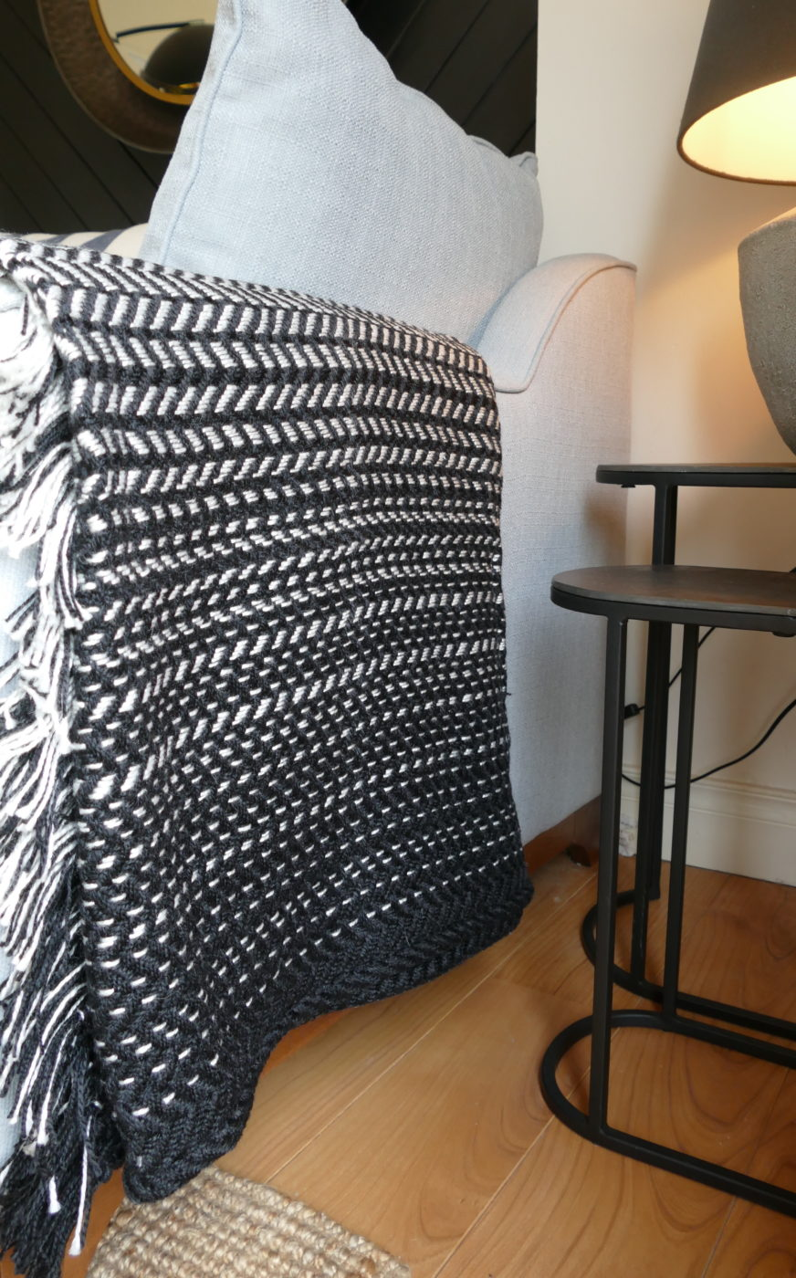 woven black and white blanket on arm of couch
