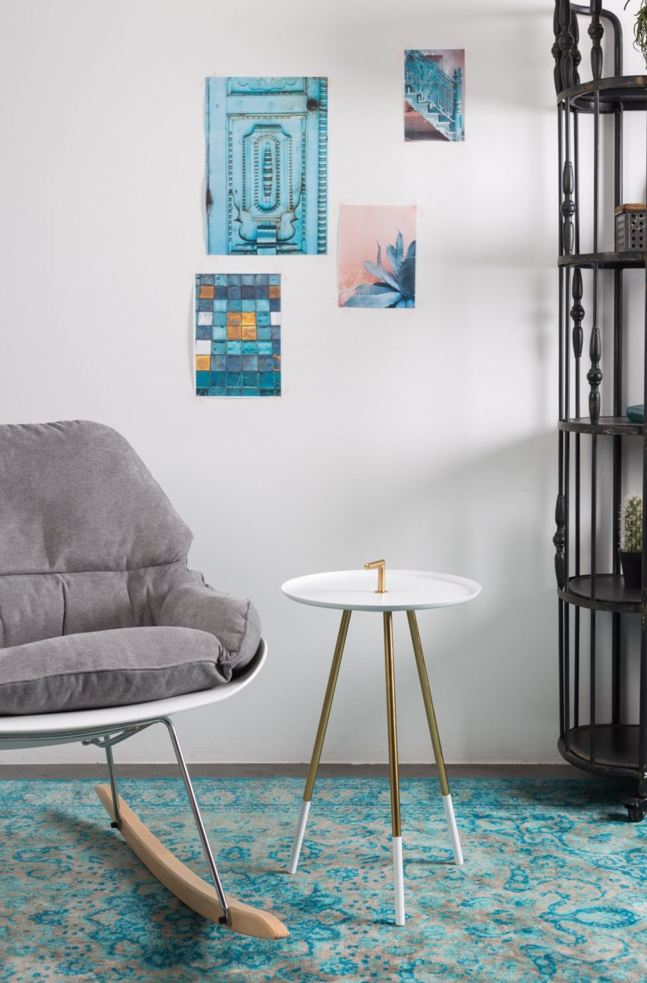 grey rocking chair on blue carpet with white side table