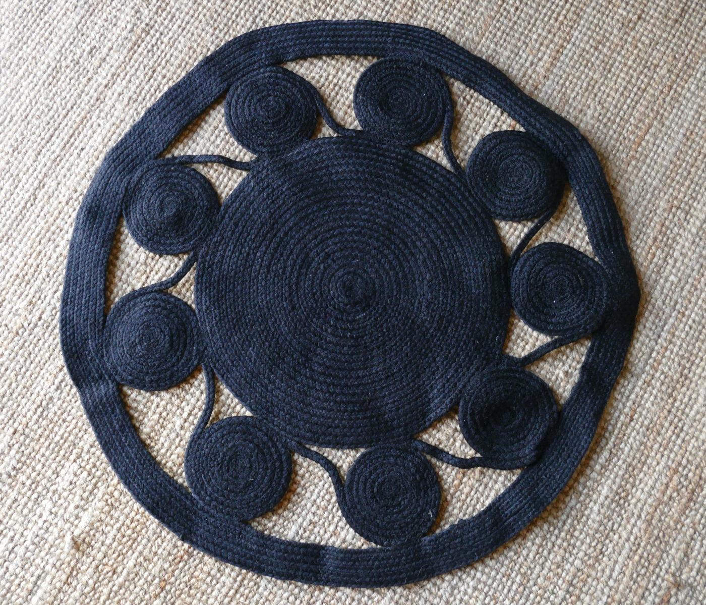 black woven rug on beige woven rug background