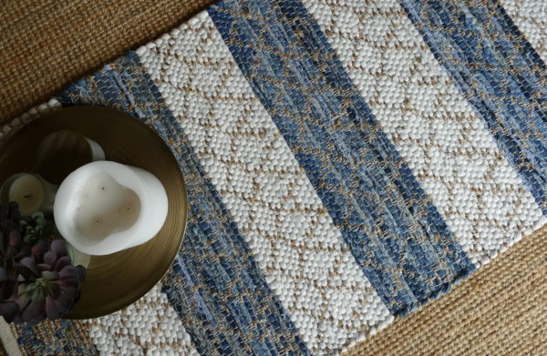 white gold and blue woven rug with tray of candles