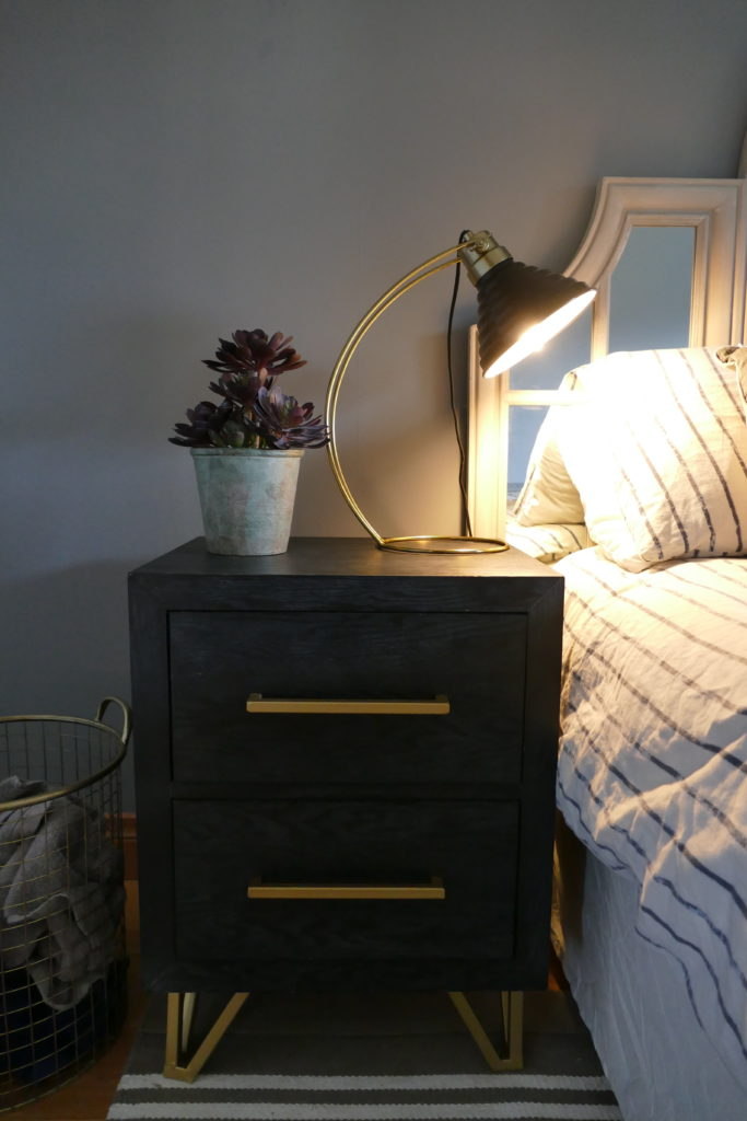 black and gold side table with lit lamp