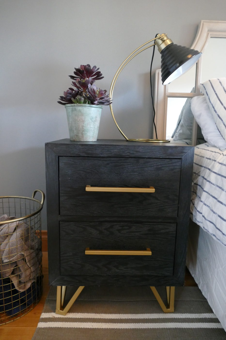 black and gold bedside table with lamp and plant