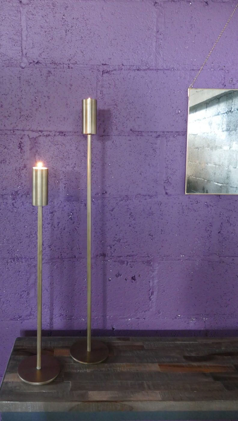 brass candle sticks against purple wall with mirror