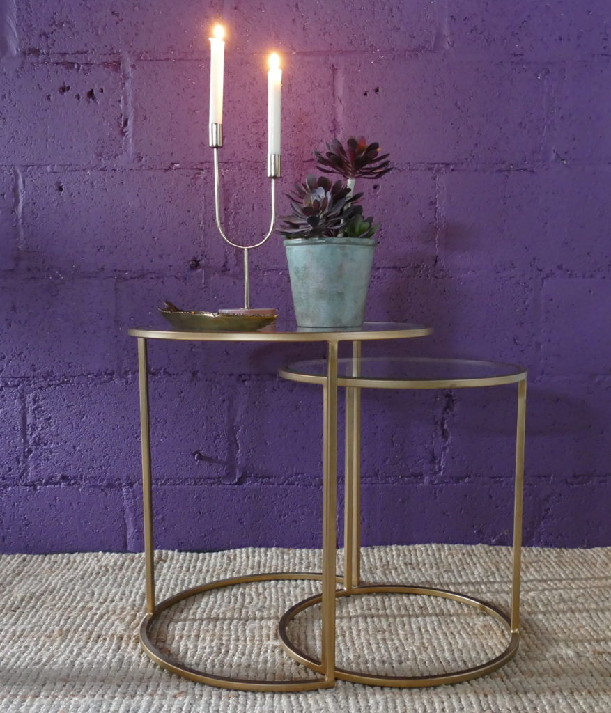 side tables gold edge with lit candles and plant