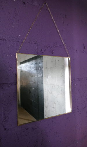 gold edge mirror on purple wall