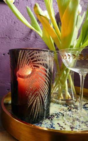 dark bamboo design candle holder beside martini glass
