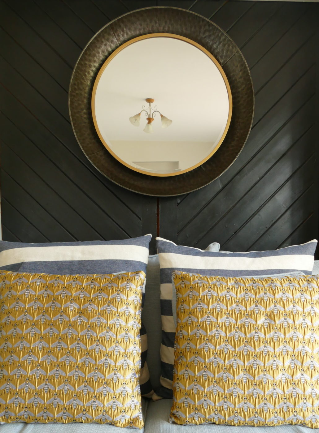 gold bee design cushions against black wall with mirror