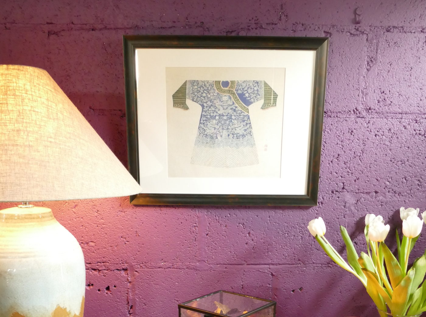 picture of blue chinese coat in frame on purple wall