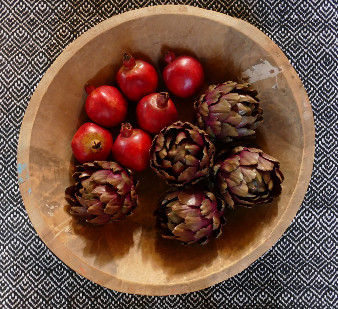 oversized wooden bowl with pomegranate and carciofi
