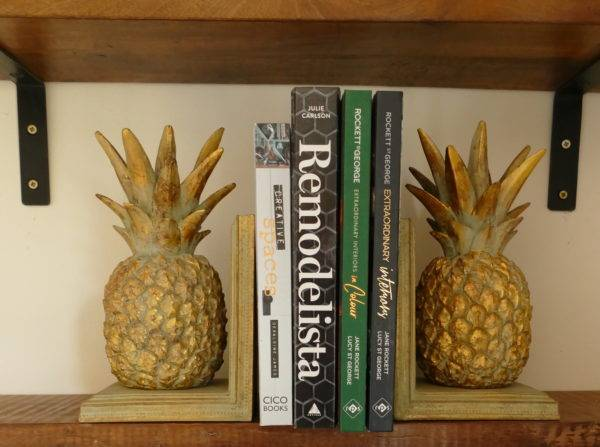pineapple bookends holding up books