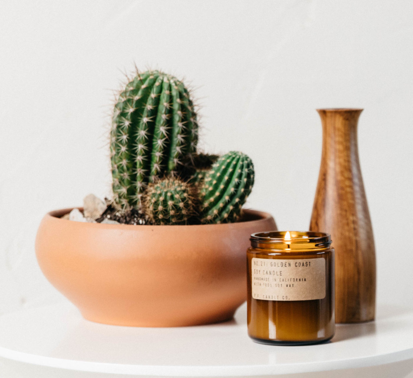 pf golden coast scented candle beside cactus