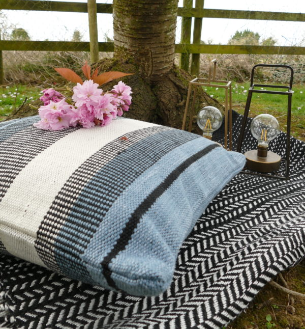 blue and grey outdoor cushion on blanket