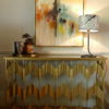 sassy gold console table with abstract painting and lamp sold by stagers lifestyle