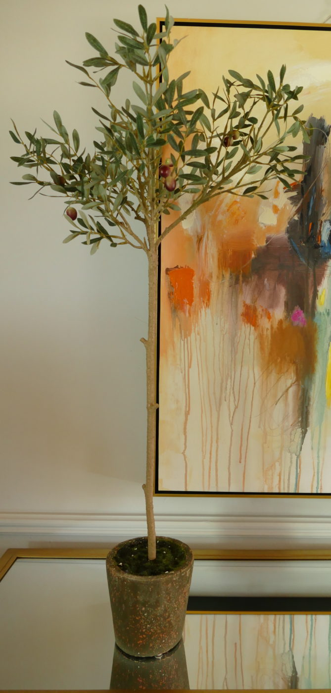 faux olive tree beside abstract painting