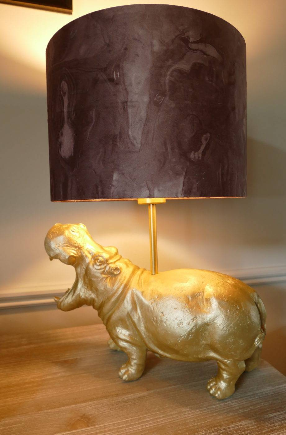 gold hippo lamp with shade turned on