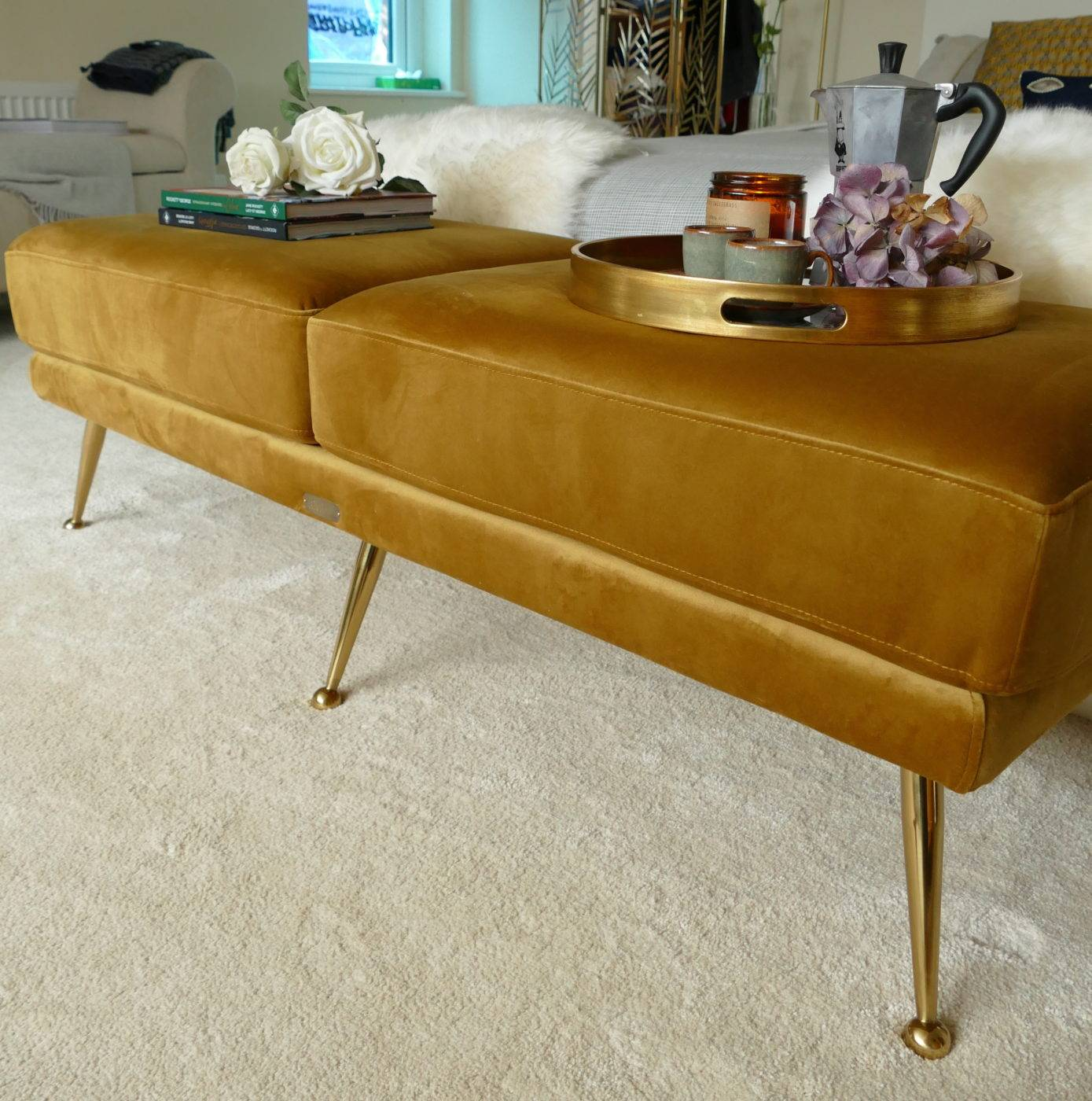 mid century mustard ottoman at the end of bed with tray