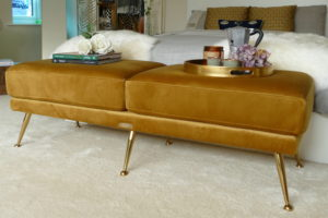 mid century mustard ottoman at the end of bed