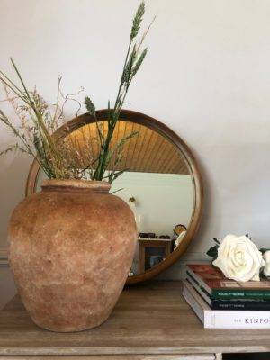 old water pot terracotta with round recycled teak wood mirror on shelf behind vase