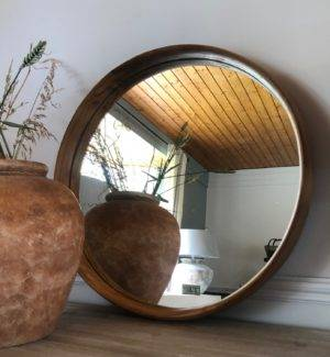 round recycled teak wood mirror on shelf