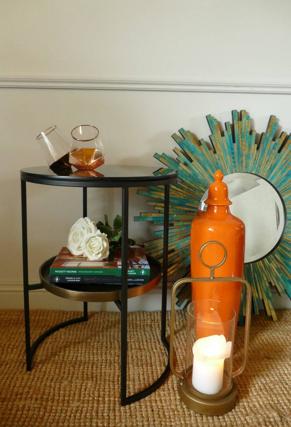 rowdy side table with glasses and books beside other stagers lifestyle products