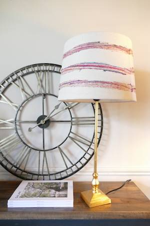 GOLD LAMP WITH PINK AND WHITE SHADE ON TABLE WITH CLOCK