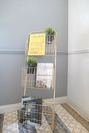 FLOOR STANDING GOLD MAGAZINE RACK ON RUG